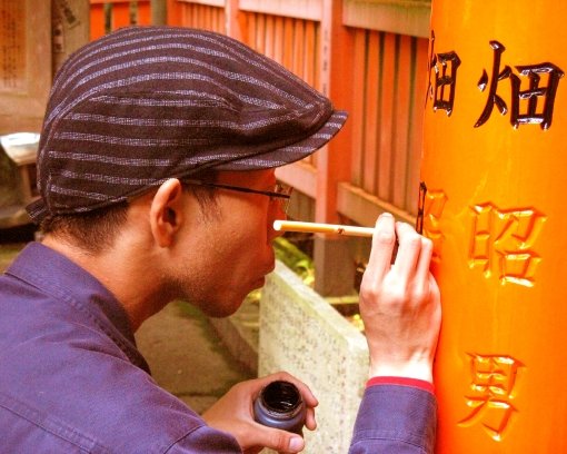 Workman putting last touches on a newly-restored torii.